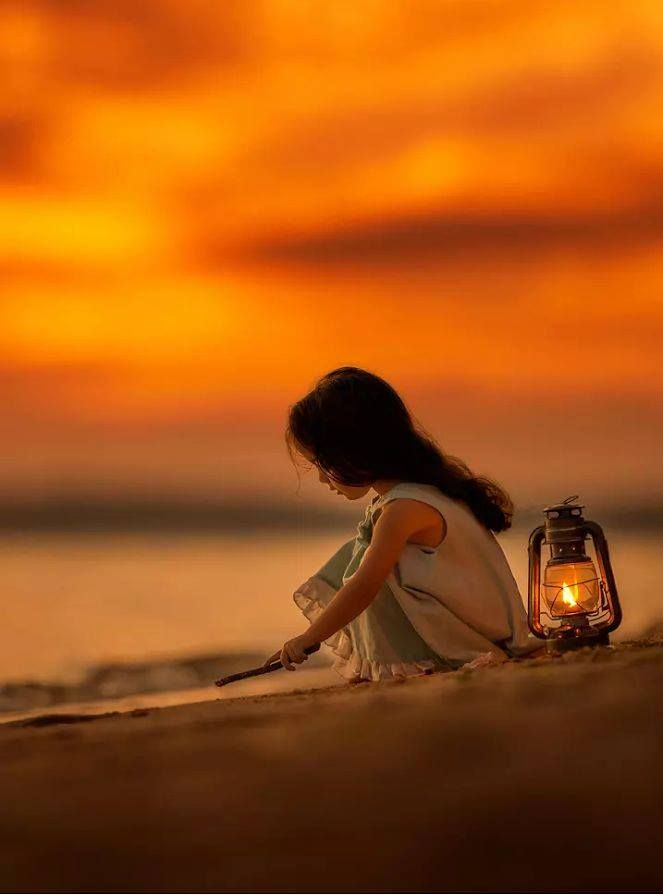 A Little Sweetheart Serenely Creates Beautiful Images in the Sand.