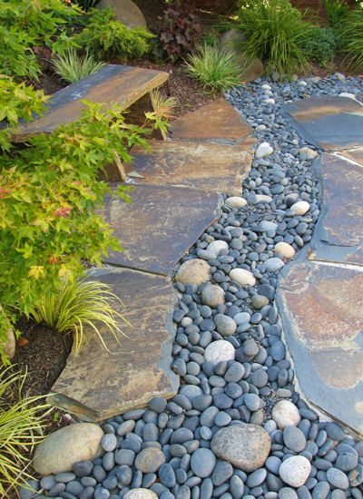 Dry stream of pebbles and river rock carves the yin and for River rock landscaping