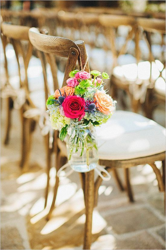 beautiful farm chairs with a padded cushion and mason jars filled with flowers