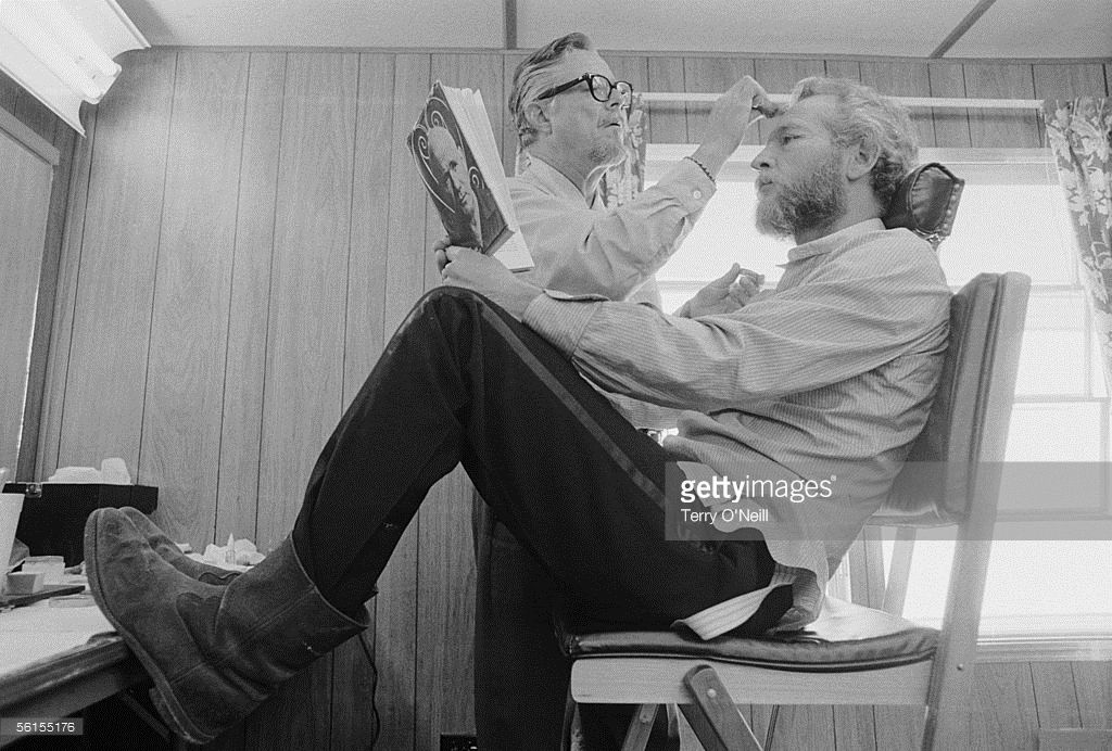 American actor Paul Newman having make-up applied for his role in John Huston's 1972 comedy western 'The Life and Times of Judge Roy Bean'.