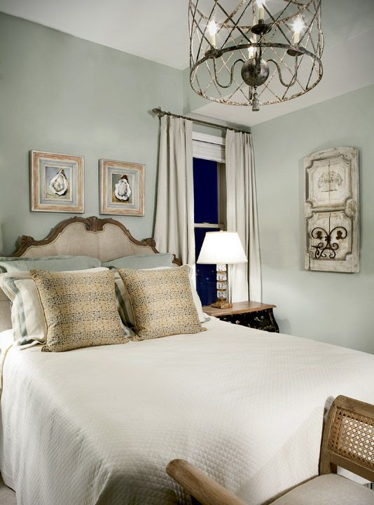 The guest room with walls painted a silver sage color and art reminiscent  of French decor. The guest room with walls painted a silver sage color and art