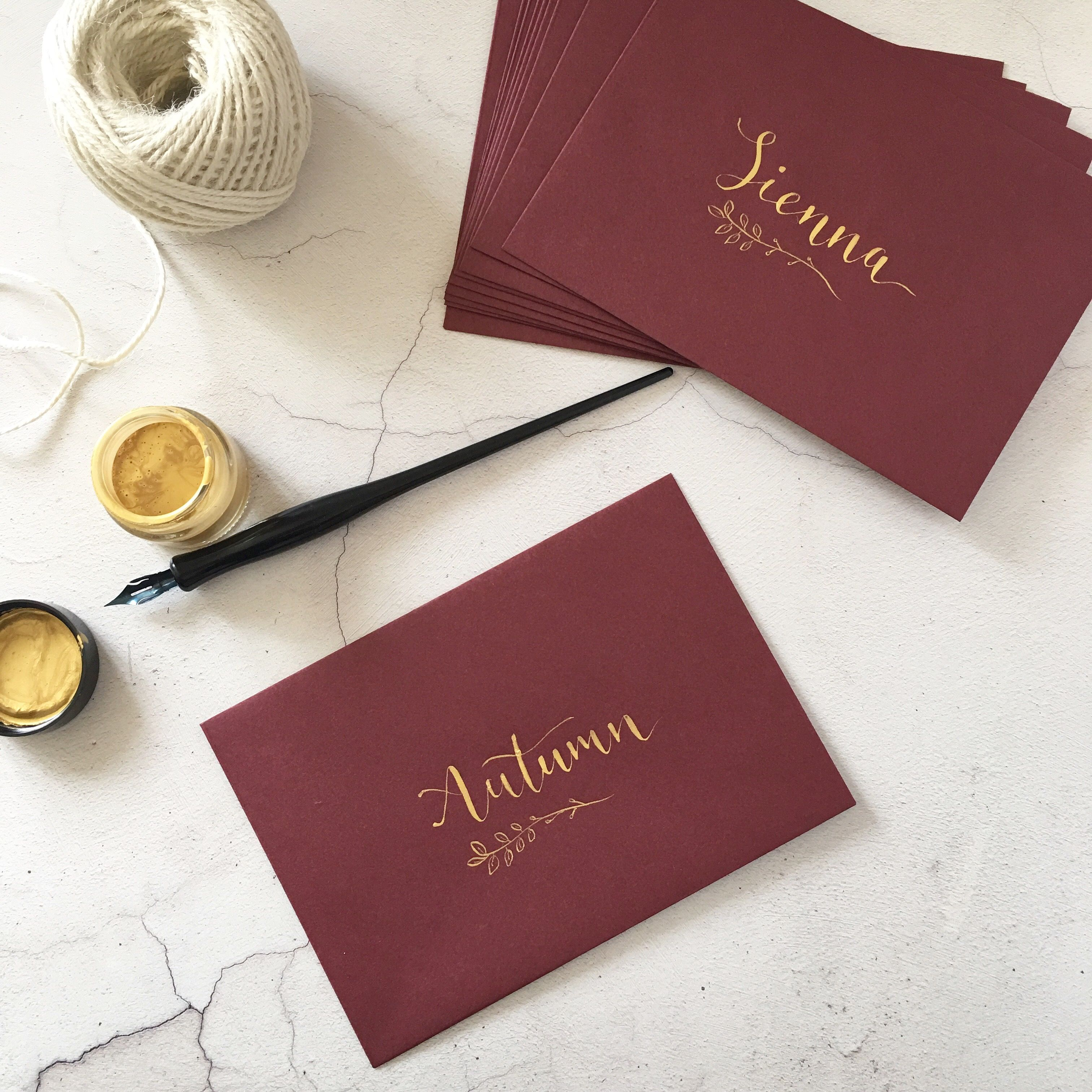 Gold calligraphy names and botanical detail on burgundy envelopes ...