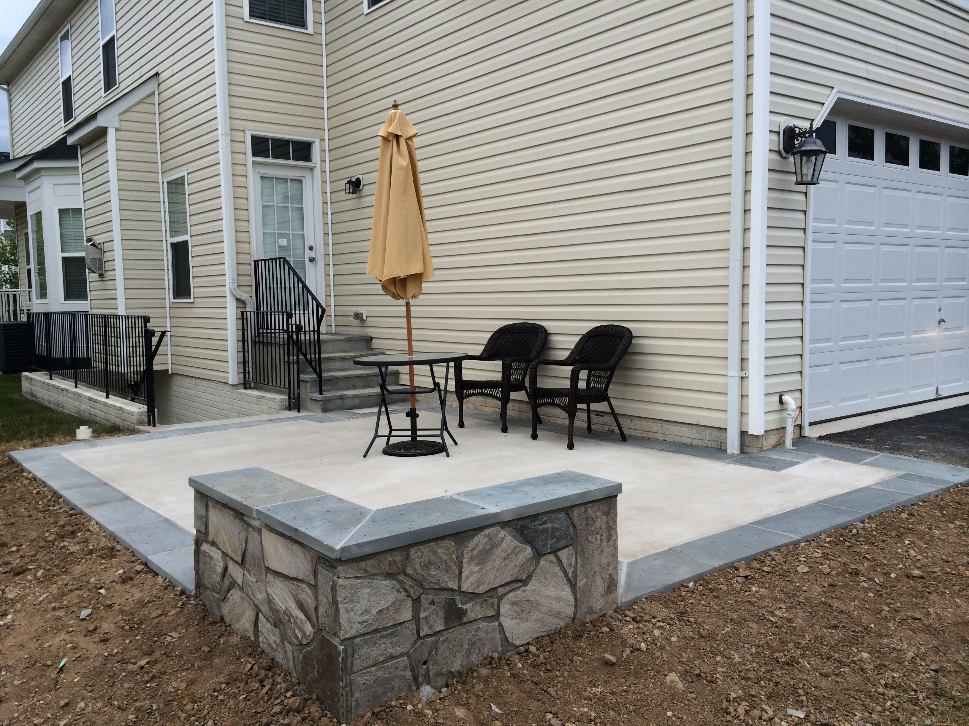 Concrete Patio With A Stone Seating Wall And Flagstone Border In Aldie Virginia Concrete Patio Backyard Landscaping Designs Backyard Landscaping