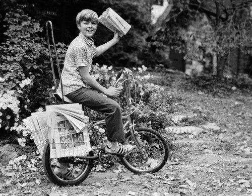 1970s Smiling Delivery Newsboy On Bicycle About To Toss Newspaper Looking At Camera Boy Bike The Good Old Days Photo