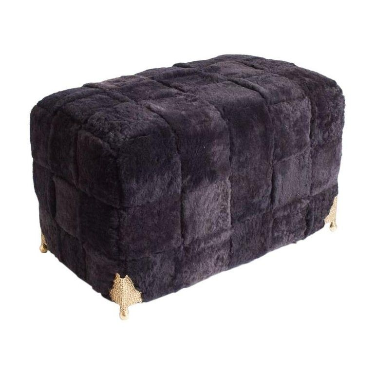 Contemporary bespoke black shearling ottoman with woven lambskin bands and brass legs.