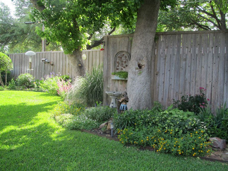 Flower bed along fence staggered instead of boring usual for Garden bed fence ideas