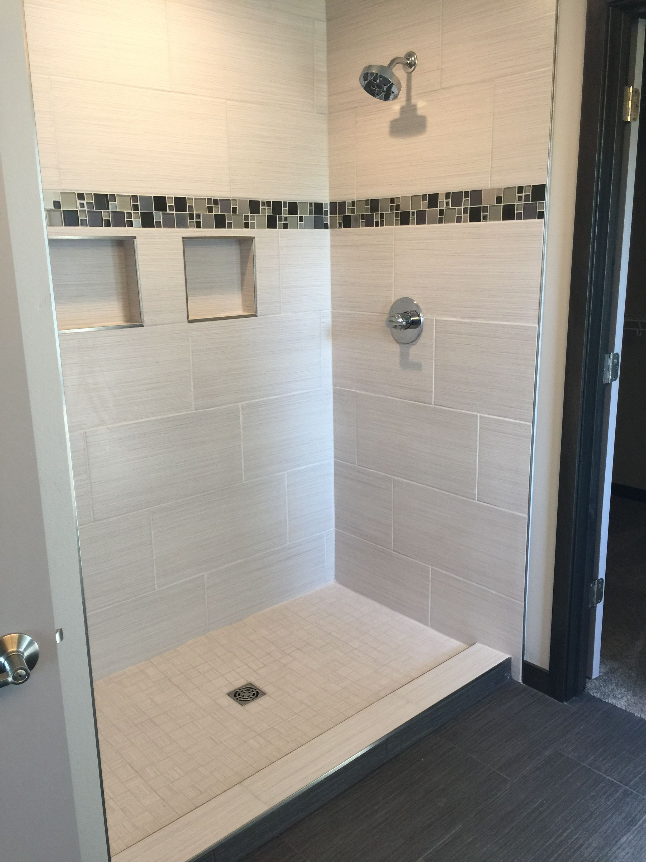 Custom Tiled Shower With 12x24 Satiated Tile Run 1 3 Staggered Vertically With A Glass And Metal Mosaic Acce Basement Remodeling Custom Tile Shower Shower Tile