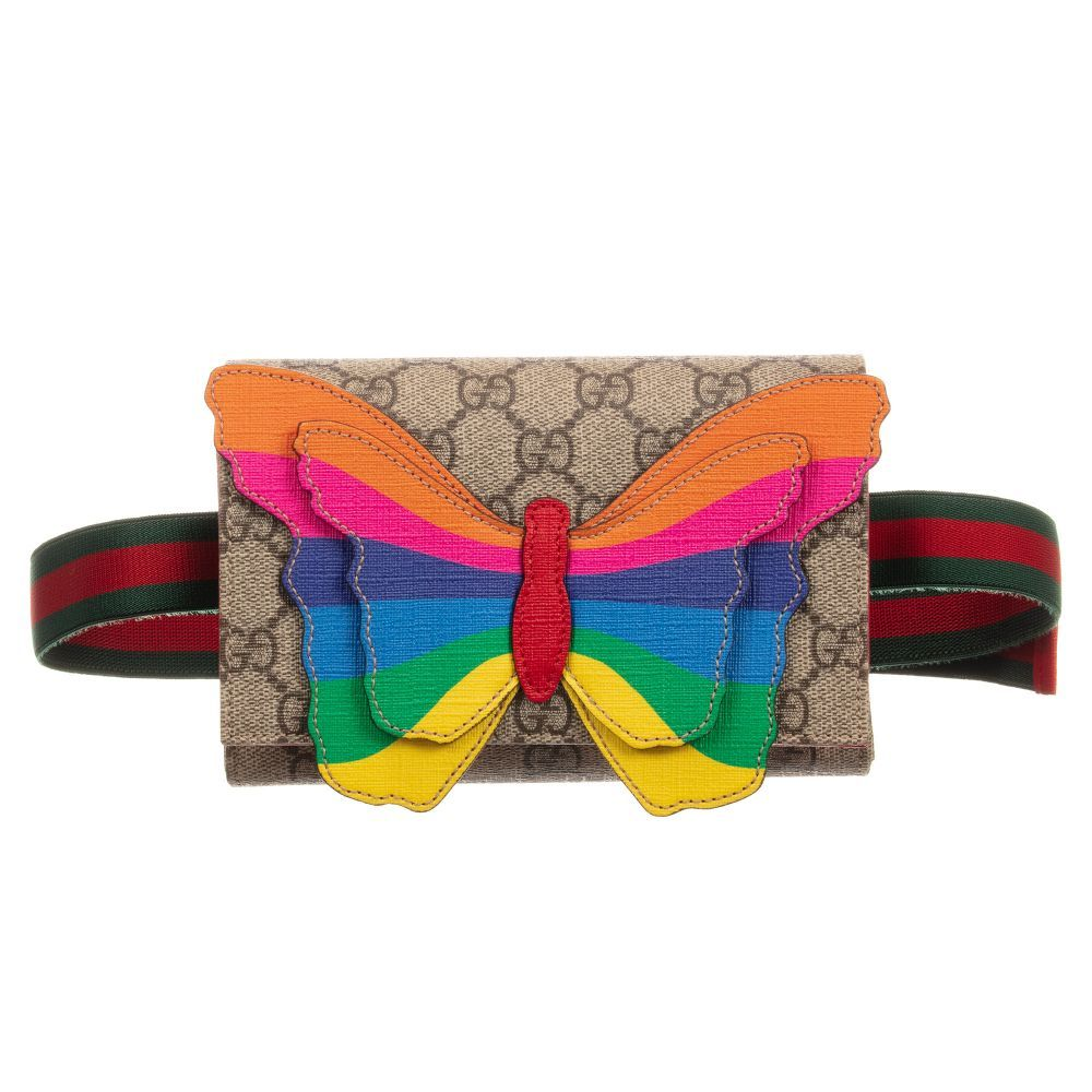 25397442a637 Girls beige Supreme canvas belt bag from luxury designer Gucci, with the  signature 'GG' logo print. It has a colorful rainbow butterfly appliqué on  the ...