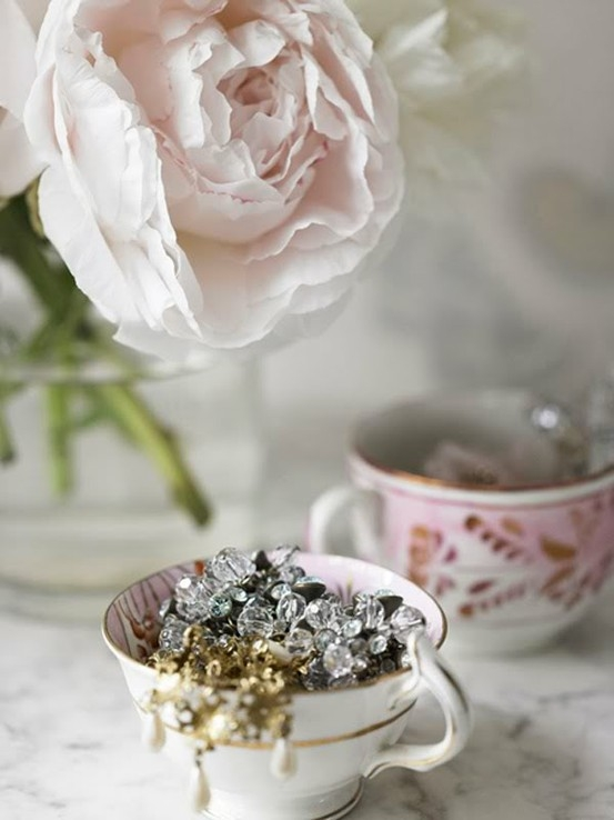 Dainty teacup filled with vintage jewelry