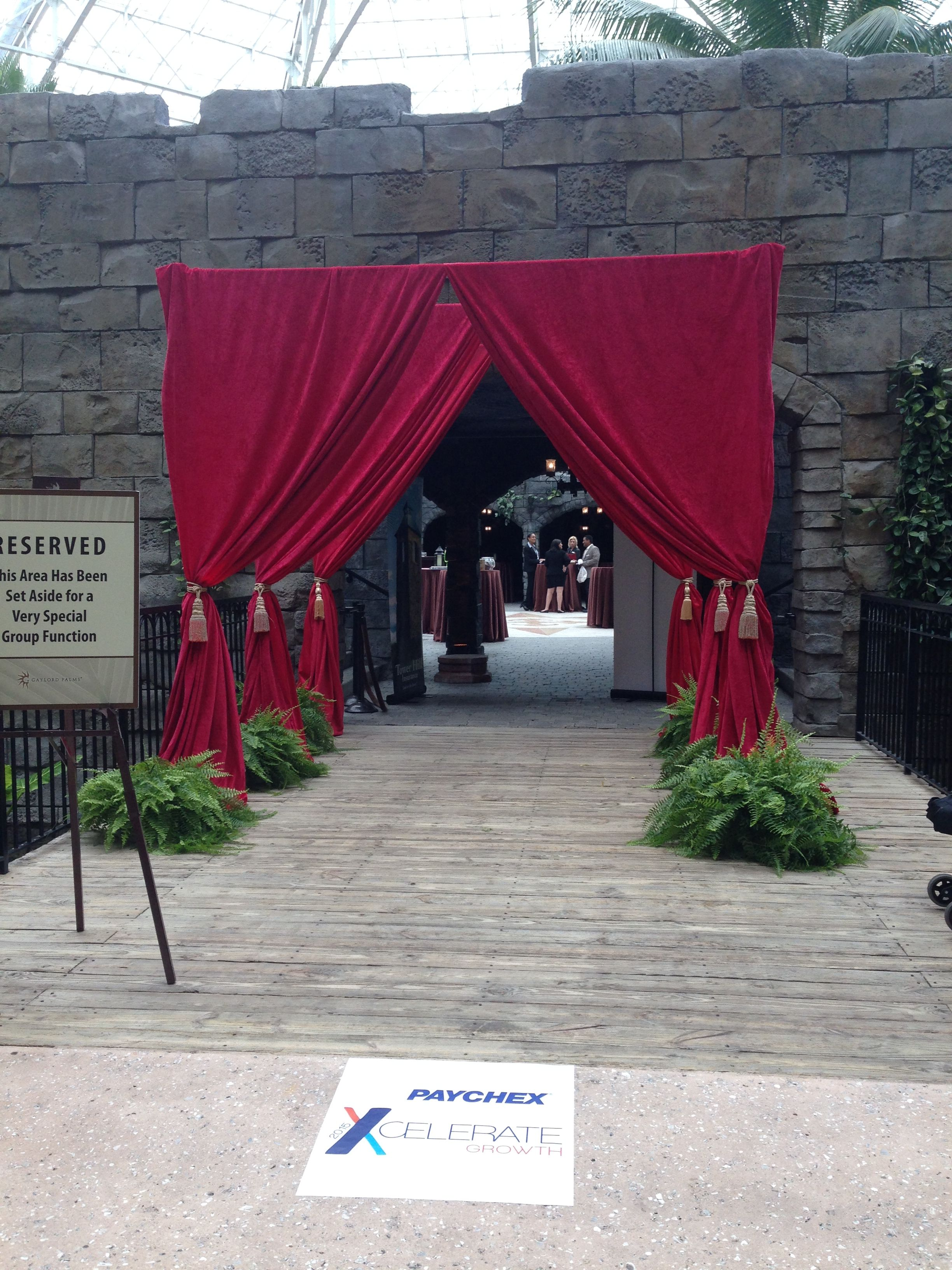 Red Drape Tunnel Entrance With Ferns And Up Light At Each Base Fleventdecor Event Entrance Event Decor Masquerade Prom