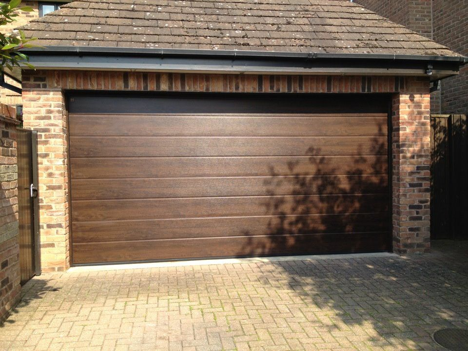 M Ribbed Hormann Sectional Garage Door In Night Oak Insulated And Remote Control For That Touch Of Luxury And Style Sectional Garage Doors Doors Garage Doors