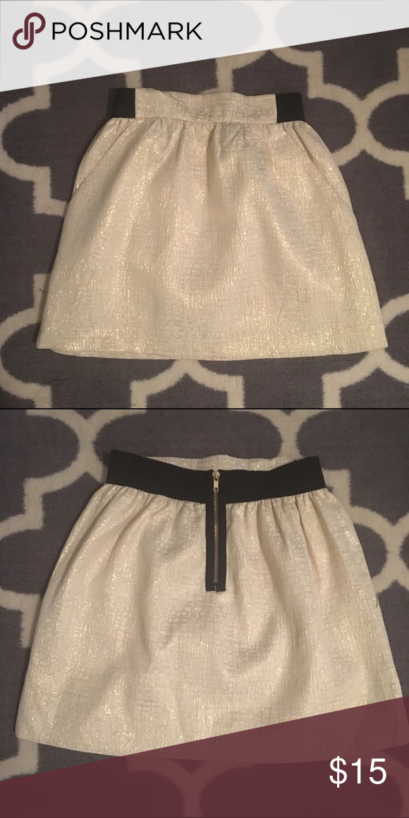 Size M Metallic Gold Skirt Beautiful skirt for the holidays! Front pockets and back zipper. Inside is lined.   Colors: Metallic gold and cream colors with black band and zippered back.  Sits higher on waist.  Brand: Charlotte Russe Material: 49% rayon, 43% polyester, 8% metallic Machine wash cold. Charlotte Russe Skirts Mini