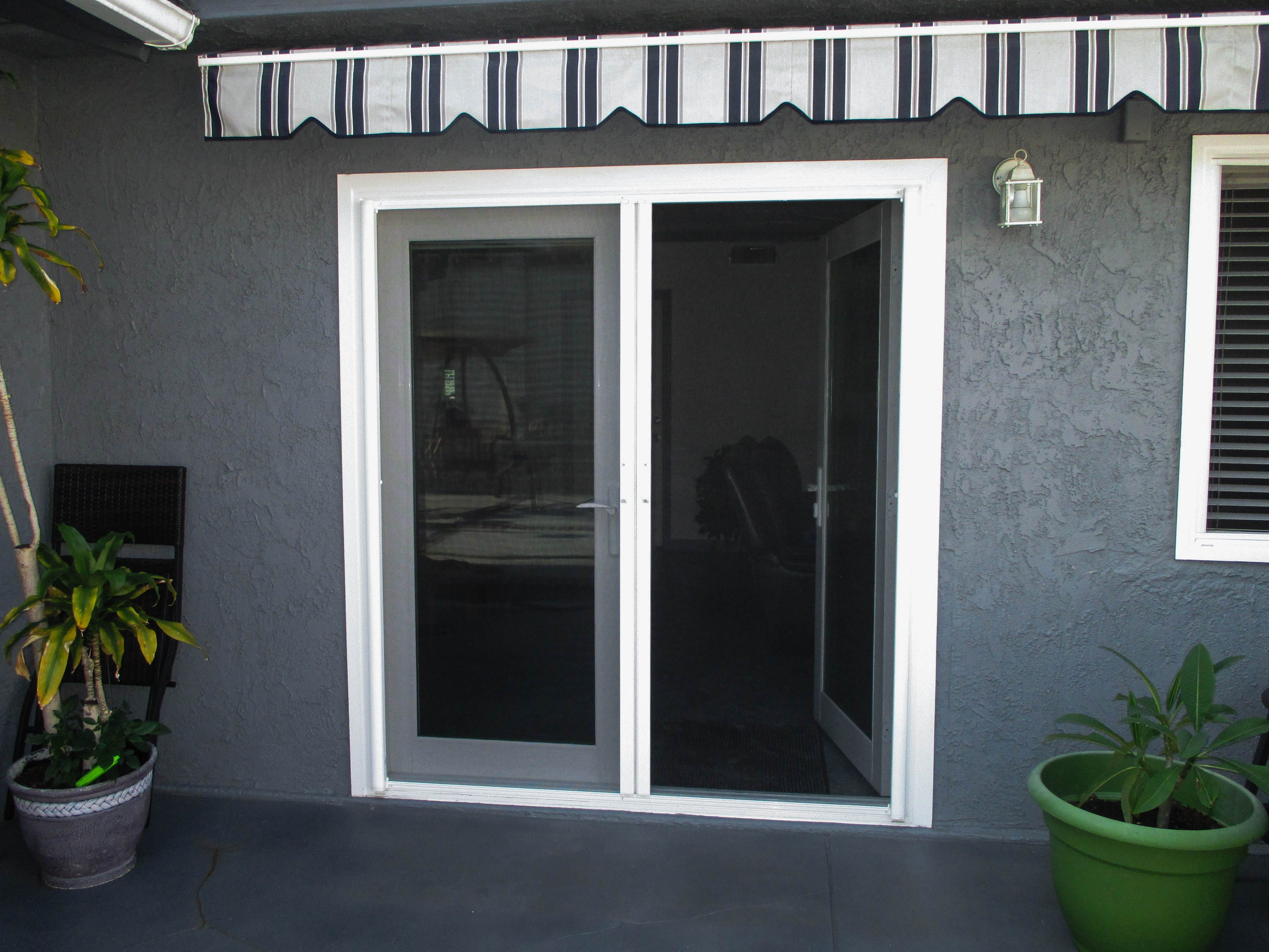 We Love The Striped Awning And White Framed French Doors Against The Charcoal Gray House We Were Ab Beautiful French Doors Retractable Screen Door Grey Houses