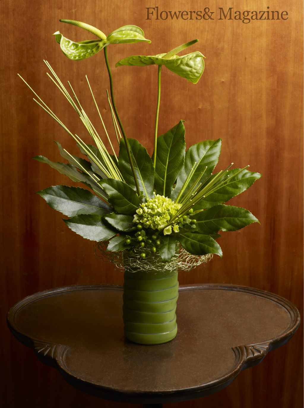 Wavy green anthuriums shelter the base of the monochromatic arrangement while hydrangea, hypericum and green midollino reinforce the radial lines of the fatsia foliage.  Design by Jim Ganger AIFD, photography by Ron Derhacopian. #flowersand  #flowers  #floraldesign