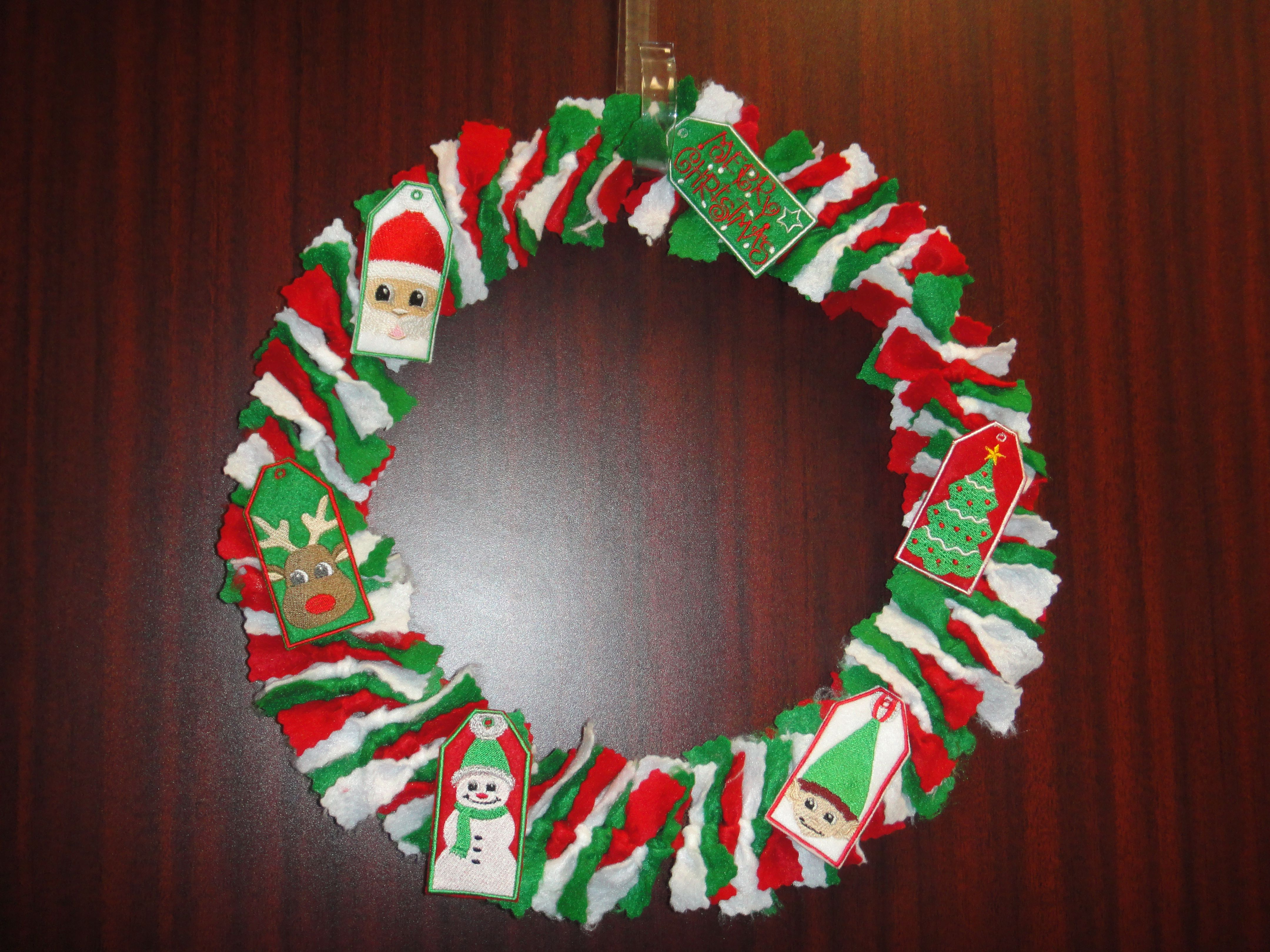 """I made this Christmas wreath for my door at work.  I made the """"gift tags"""" on my embroidery machine."""