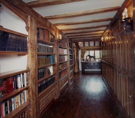 Tudor Interiors library | Tudor arched oak bookshelving and oak panelled  passageway