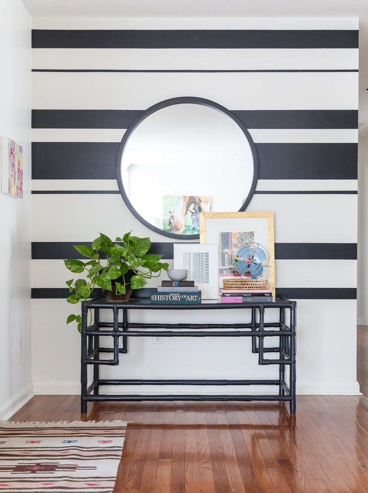 The painted stripes give this wall of the entryway a bold touch