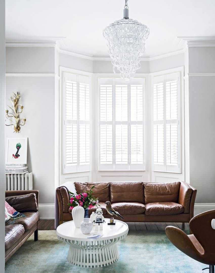 White Modern Living Room With 1960s Style Sofa And Chandelier The Room Edit Living Room White Leather Living Room Furniture Modern White Living Room