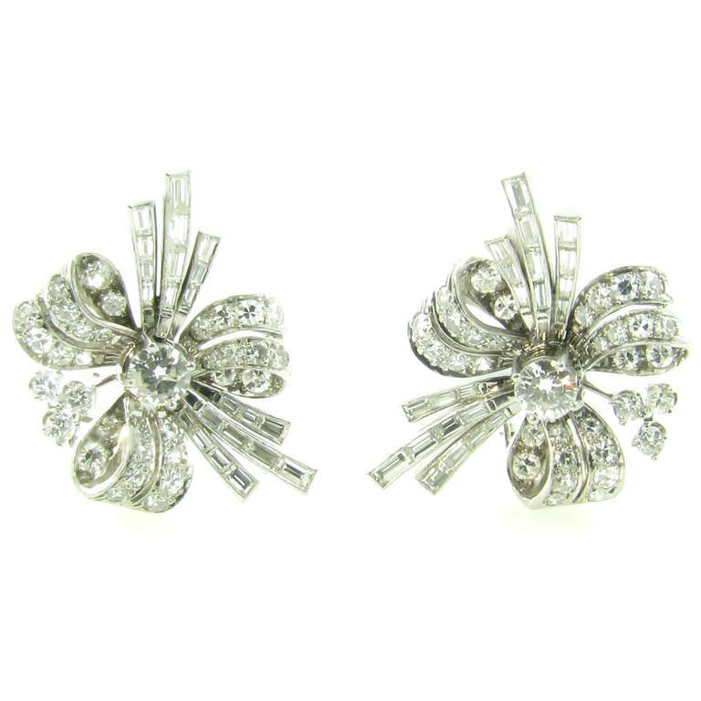 A Pair of Art Deco Platinum and Diamond Earrings. A pair of Art Deco platinum and diamond earrings with 14 karat white gold earclips, circa 1930s. The earrings are in the shape of stylized bows, c 1930