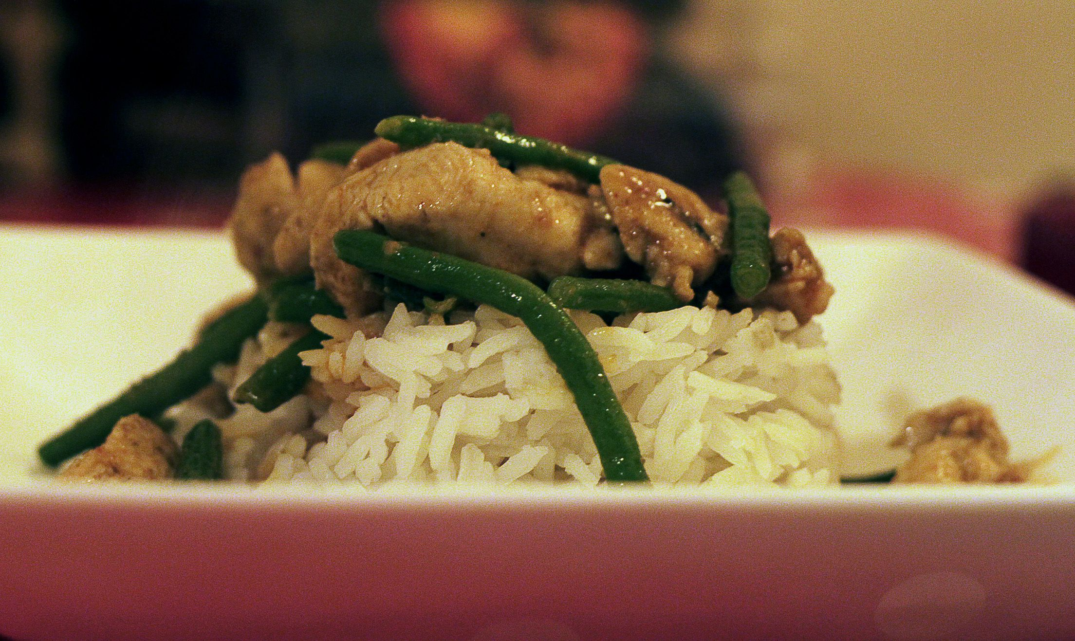 Chicken breast with green string beans and cherry tomatoes in coconut milk with a hint of red curry paste served with steamed white rice