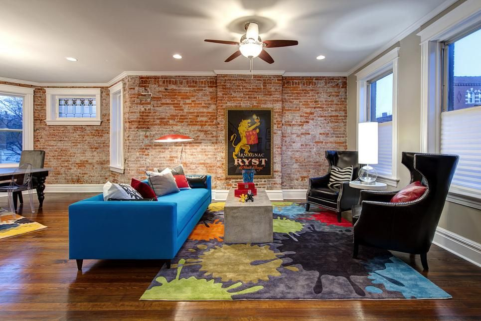 The long brick accent wall lining this living room adds warmth and