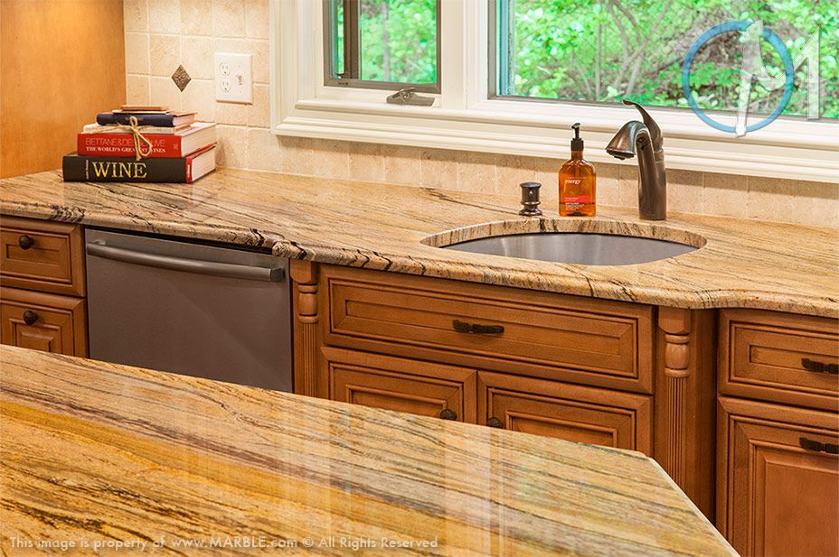 The Warm Colors Of The Stone And Cabinets Give This