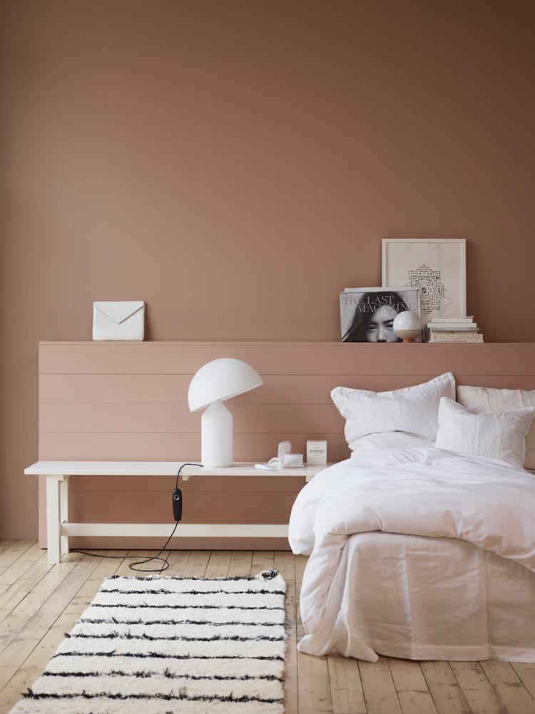 Camera accogliente in rosa antico e pavimento in legno. Cosy bedroom ...