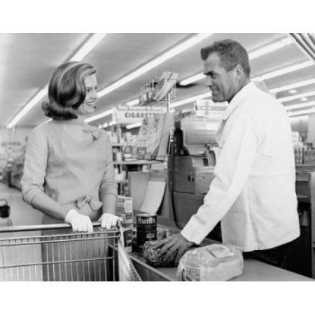 Mid adult woman and a male sales clerk at the checkout counter in a super market Canvas Art - (18 x 24)