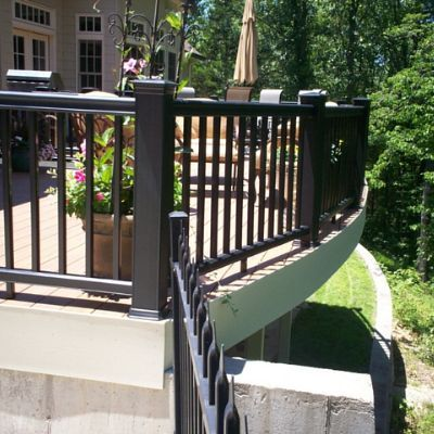 This custom elevated vinyl deck with curved TimberTech ...