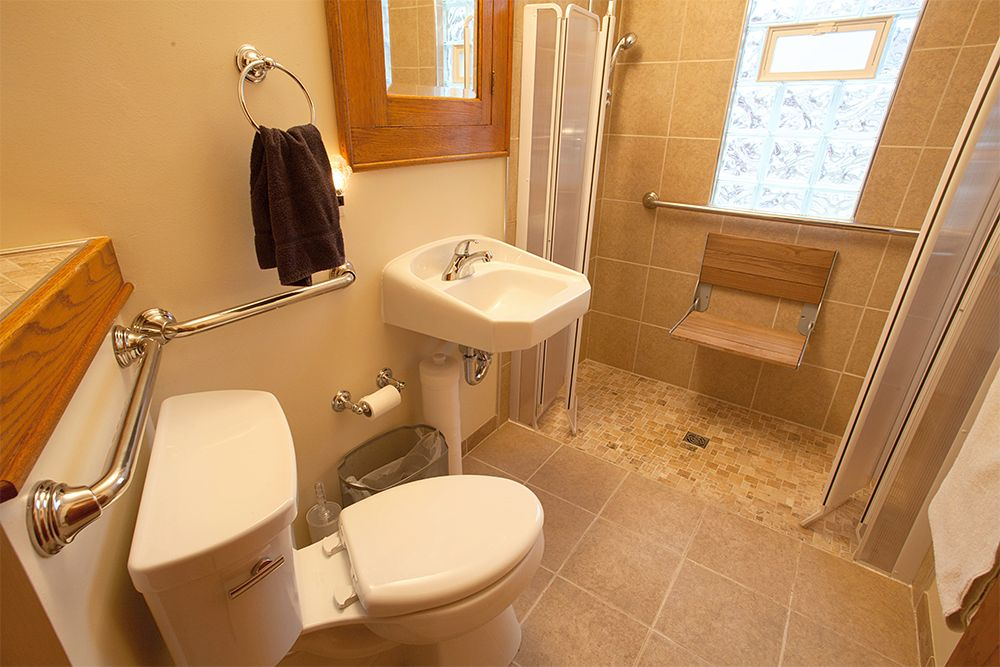 Custom built, zero threshold, tiled shower with teak flip-down seat ...