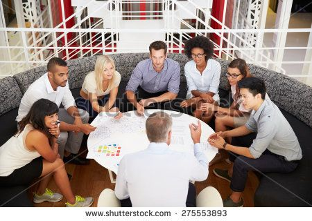 Group of work colleagues having meeting in an office lobby - stock photo