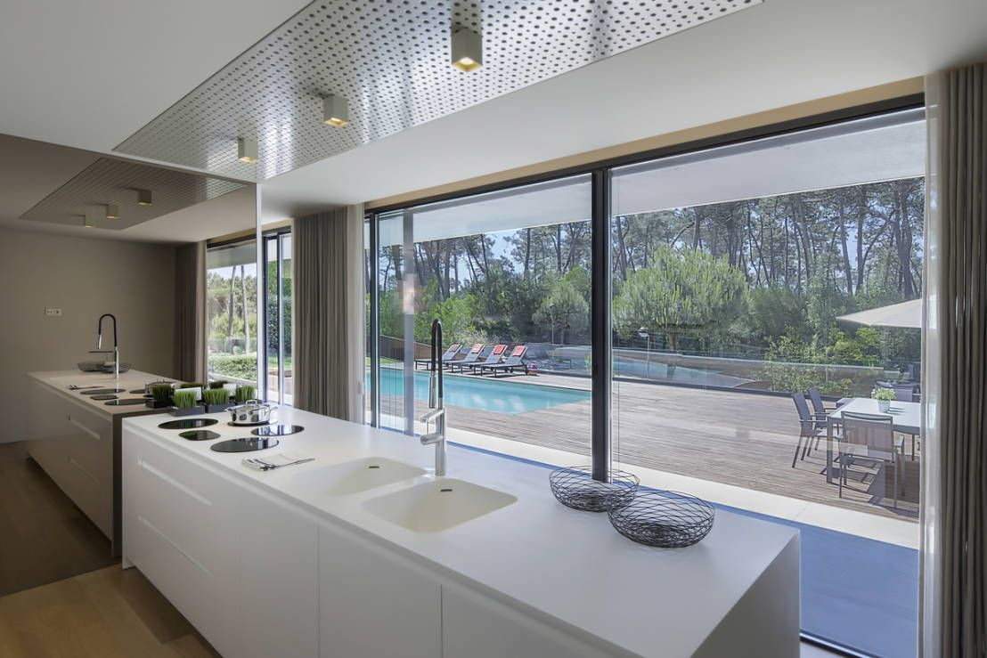 Stunning modern kitchen with white cabinets and bench tops, looking out onto a pool and patio area. So chic, modern and minimal. By INAIN® interiordesign