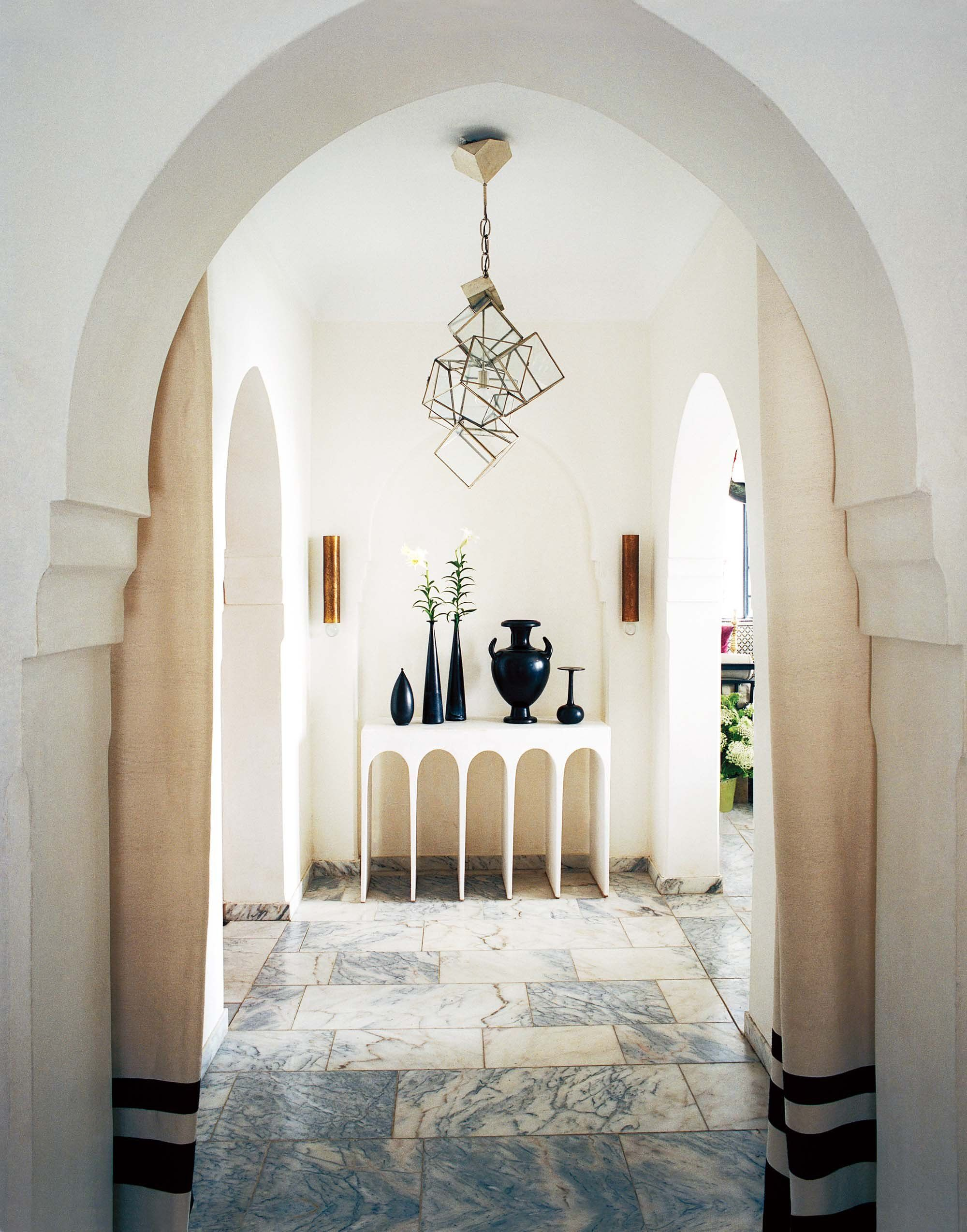 The Moorish arches give away the Moroccan location of designer Bruno Frisoni's Tangier retreat, and the light fixture and arched console, designed by Frisoni's partner, Hervé Van der Straeten, bring a modernity to the historic house.
