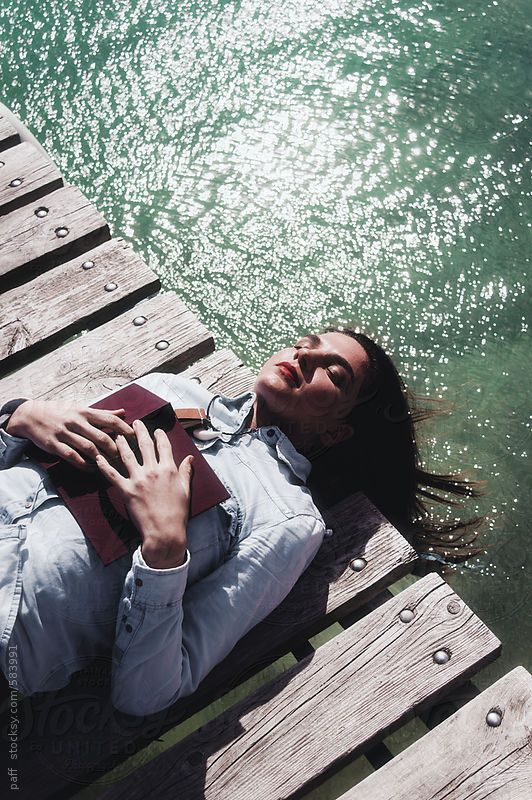 Girl holding a book taking a nap on a jetty on a summer day by paff | Stocksy United