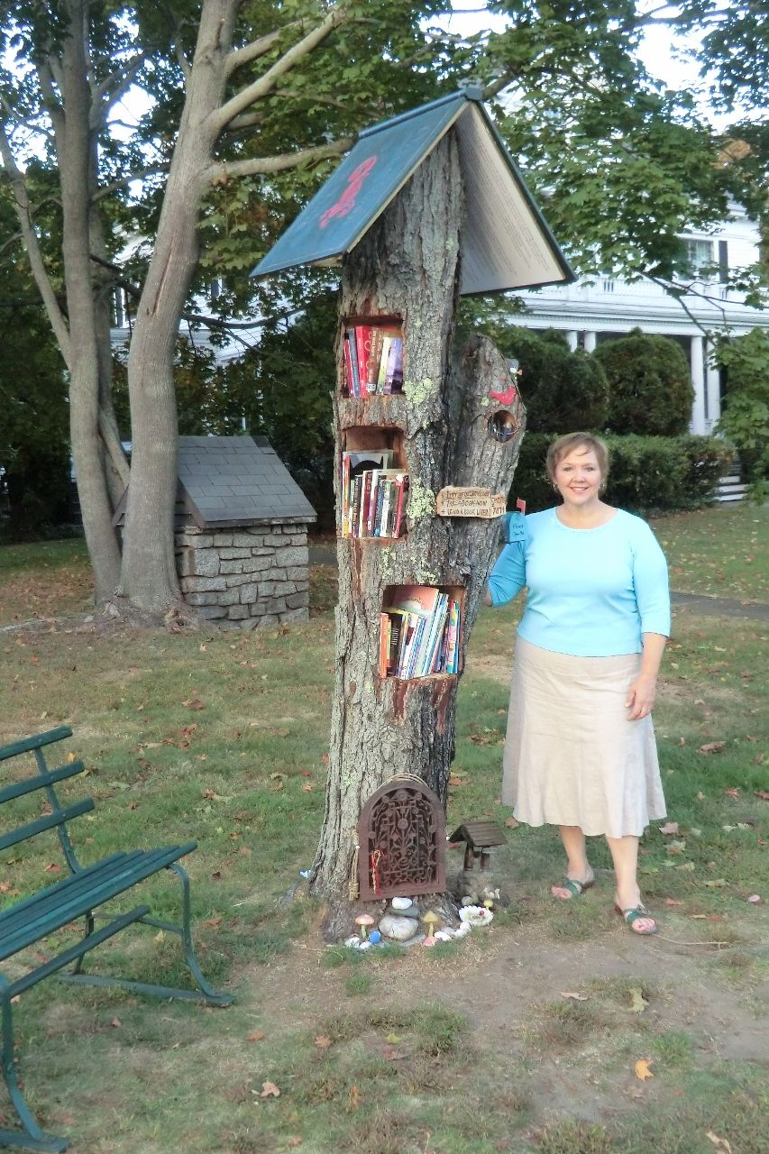 """Lynn Blume. Hampton, NH. We had a tree cut down in the front of our yard so we created a LFL out of the trunk. So far we haven't needed doors b/c the fairy tale book roof protects the books! My daughter and her boyfriend created the dragon and sword on the roof. It has been a joy to see parents stop and sit with their children to read. A fairy resides in the tree and often people will leave """"their musings"""" for him on the notepad left in a tiny mailbox. He often writes back, always after his…"""