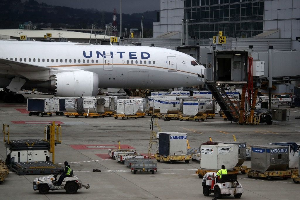A United Airlines plane sits parked at a gate at San