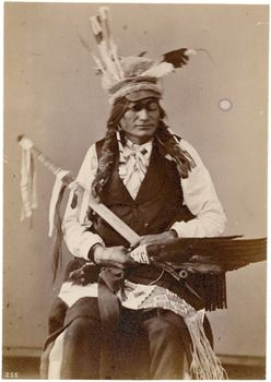 Description:Studio seated portrait of Chief Kan-Gi-I-Yo-Tan-Ka or Kah-Re-Eo-Tah-Ke or Sitting Crow, wearing feathered cap with high crown and brim, fur-wrapped braids, pipebead choker necklace with metal(?) beads, white shirt and tie, dark vest, lower body wrapped in a blanket with a quilled or beaded blanket strip; he holds a feather fan, pipe with pipestone bowl and ribboned stem, and a quilled (and beaded?) fringed bag, and wears goggles or sun glasses. Member of an 1872 Delegation…
