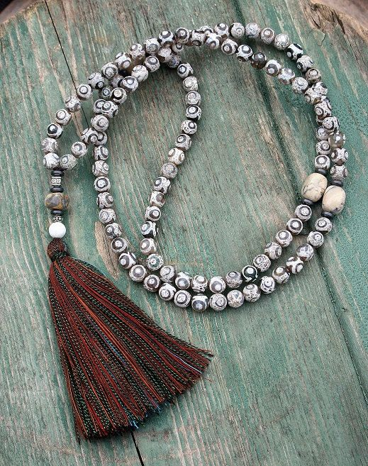 Mala made of 108, 8 mm - 0,315 inch, faceted Tibetan style agate gemstones and decorated with african opal.    The mala has a total length of