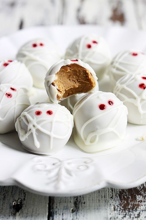 To make the dough for these no-bake mummy bites, combine gingersnap cookie and graham cracker crumbs, pumpkin puree, powdered sugar, and softened cream cheese. Cover with white chocolate and use a dab of red food coloring for the eerie eyes. .