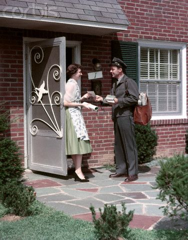 1950s Mailman Delivering Mail To Woman Brick Suburban Home