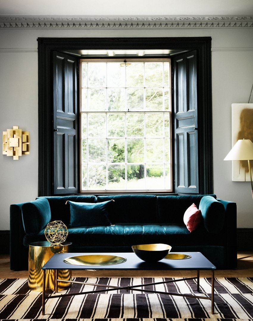 sophisticated living room with teal sofa and brass accessories