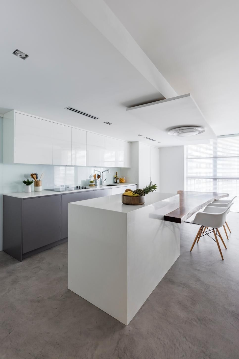 Glossy White Cabinets Without Knobs Or Handles Create A Streamlined Look In  This Modern Kitchen.