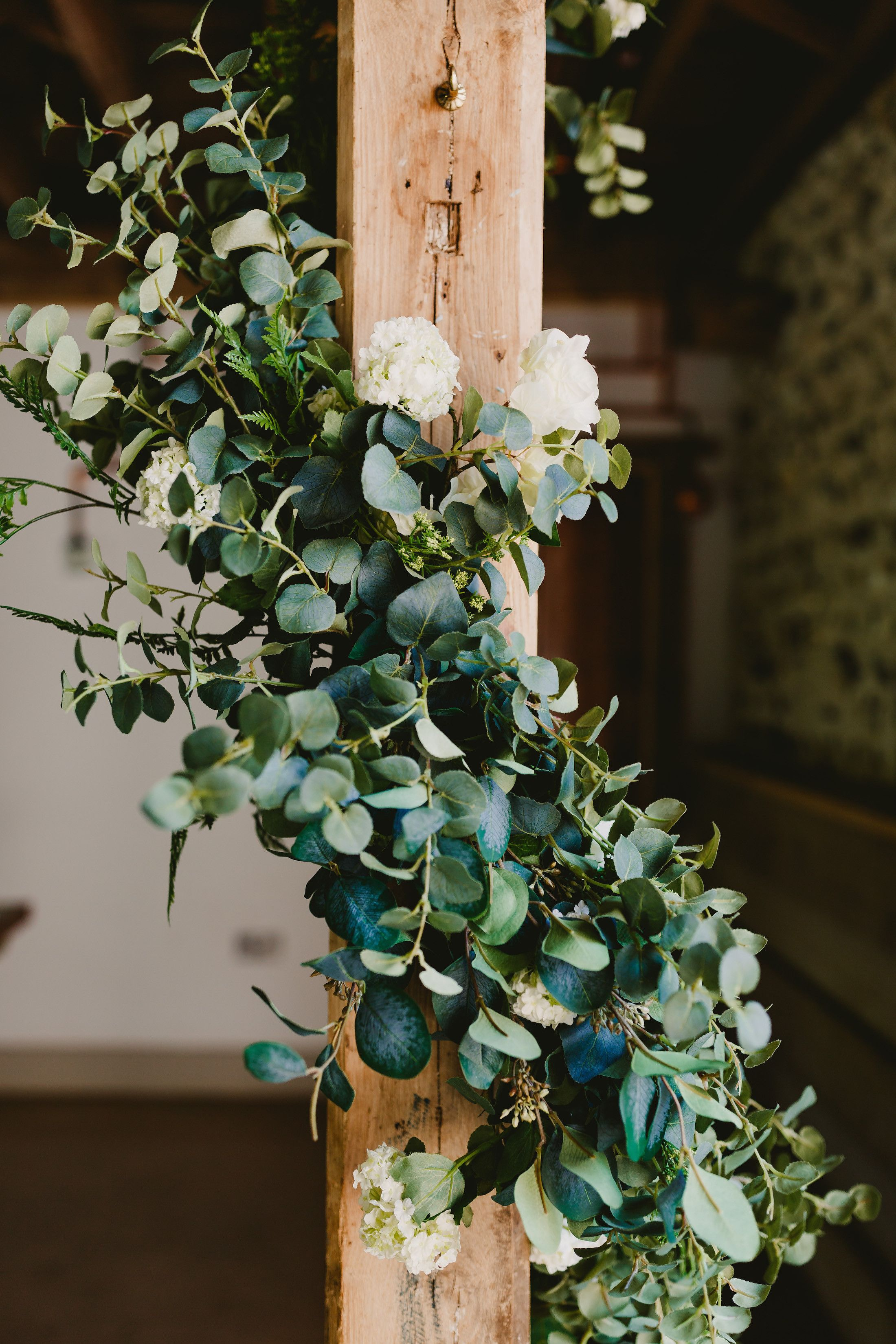 Slate blue wedding decor  Faux greenery wrapped around a beam for a barn wedding Hire these