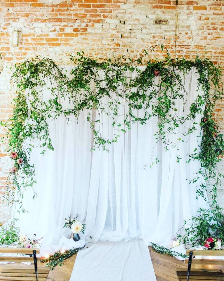 white draped wedding backdrop with draped greenery ...