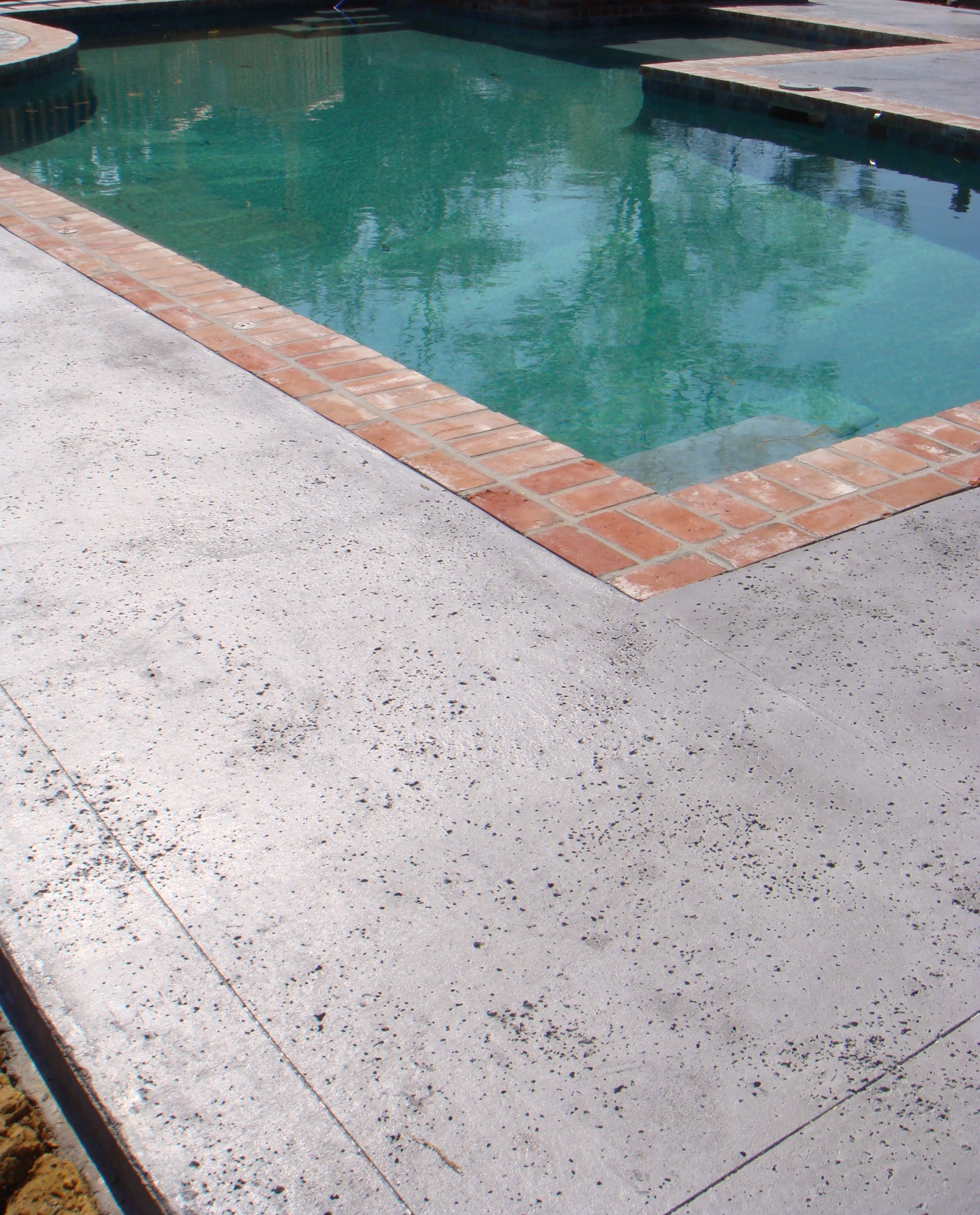 Stamped concrete with salt rock texture by nu crete for Design of swimming pool concrete