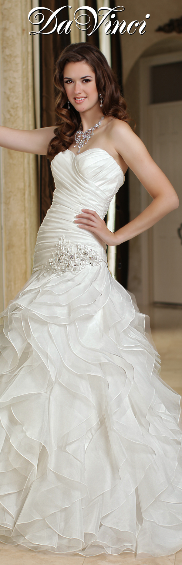 DaVinci Bridal Style # 50178 Organza gown with a pleated bodice consisting of a sweetheart strapless neckline. Dropped waist is accented with floral embroidered detail and leads to a full skirt of vertical ruffles. Lace up back. http://www.davincibridal.com/