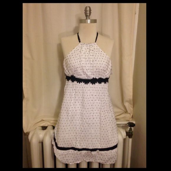 Black and white halter dress This cute halter dress is fully lined, 100% cotton, and a flattering a-line shape. The fabric has small embroidered black dots in addition to black ribbon and flower appliqués at the waist. No stains or discoloration! Dresses