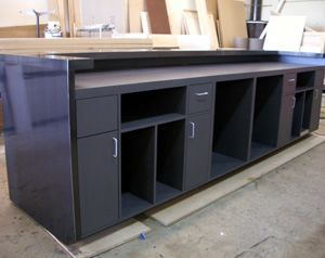 Custom Cash Wrap Cabinet Made Of Gray Laminate And Claded With Black Iron.