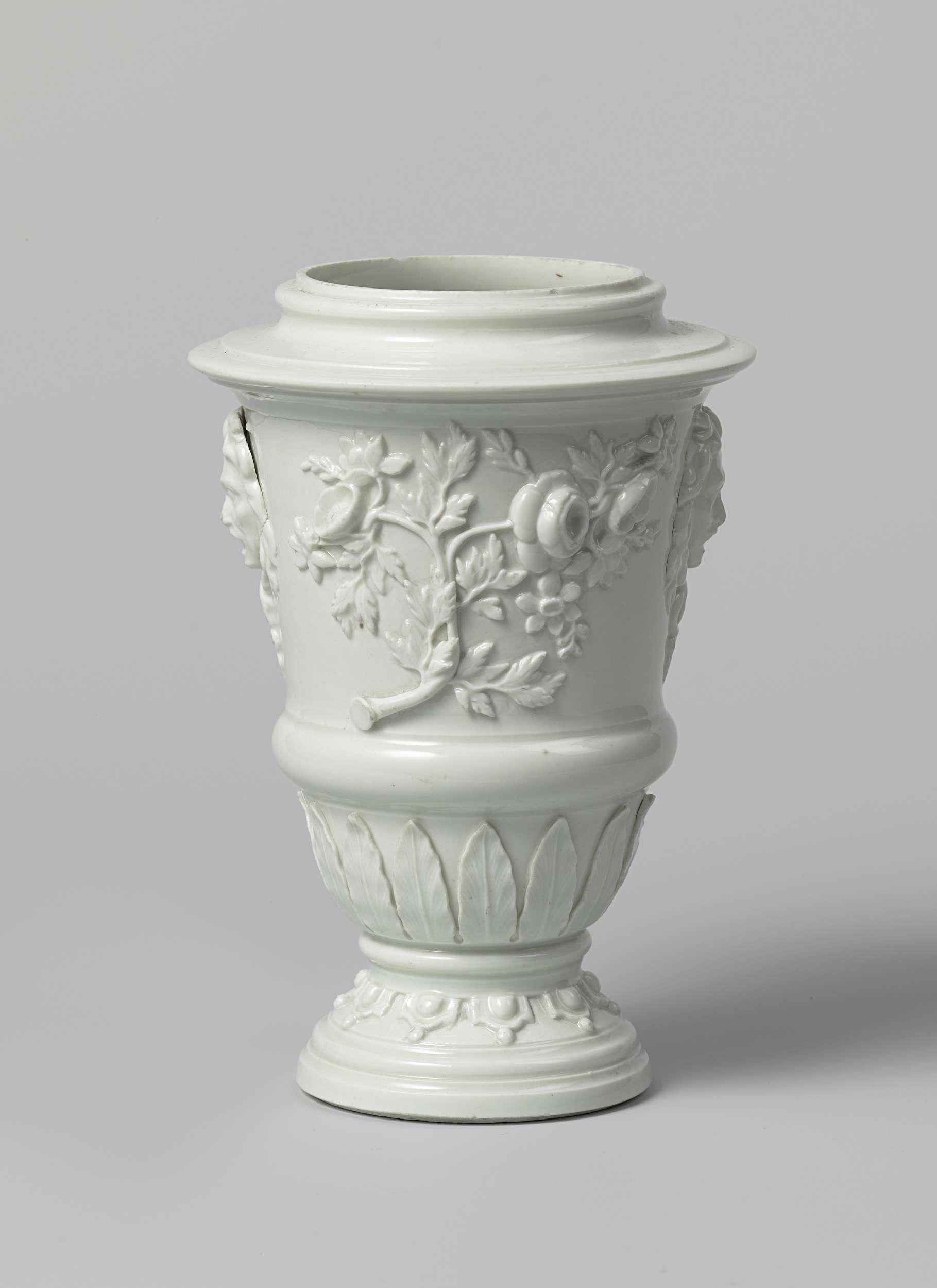 Meissener Porzellan Manufaktur | Vase, Meissener Porzellan Manufaktur, c. 1715 | Vaas van Böttger-porselein. De geprofileerde voet is versierd met een fries van lambrekijns in reliëf. Tussen de voet en het lichaam bevindt zich een platte ring. Over het onderste deel van het lichaam loopt een fries van lancetbladeren in reliëf, waarboven een geprofileerde band. Het bovenste deel is aan voor- en achterzijde gedecoreerd met rozentakken in hoogreliëf, waartussen twee geappliqueerde…