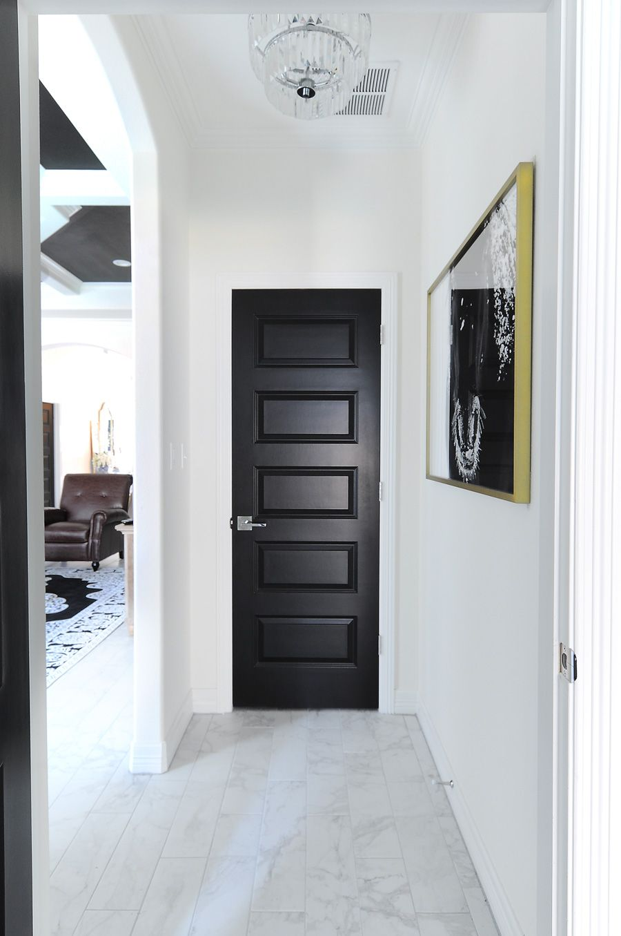 Black interior doors make a bold statement against white walls in this modern home with traditional touches